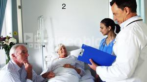 Doctor discussing report with senior couple