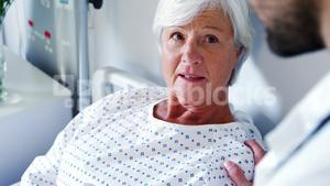 Male doctor discussing medical report with senior woman on digital tablet