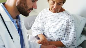 Male doctor discussing medical report with female patient on digital tablet
