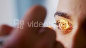 Hand of male doctor examining female patient eyes