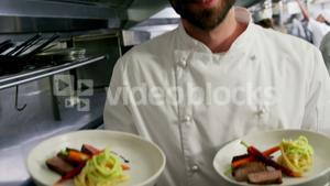 Happy chef presenting his food plates