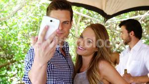 Happy couple taking selfie with mobile phone at bar counter