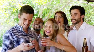Group of friends taking selfie with mobile phone at bar counter