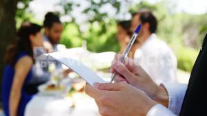 Waitress writing on note pad at outdoor restaurant