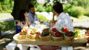 Waiter serving appetizers to couples