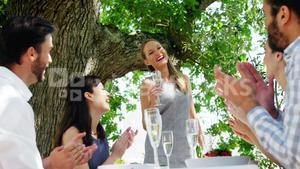 Friends at outdoor lunch applauding for woman