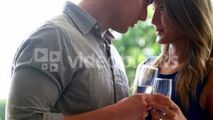 Couple looking face to face and holding champagne flutes in restaurant