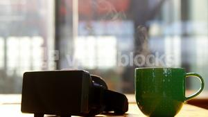 VR headset and cup of coffee on desk