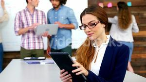 Business executive using digital tablet in meeting