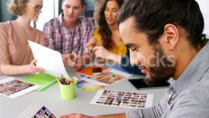 Man holding photos while business executives using laptop in meeting