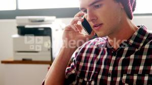 Business executive talking on mobile phone while working on laptop