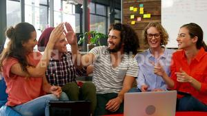 Business executives giving high fives while working in office