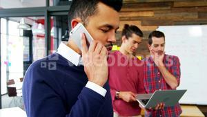 Business executive talking on mobile phone while colleague working in background