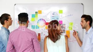 Business executives writing on white board with marker