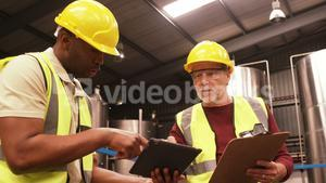 Worker using digital tablet while writing on clipboard