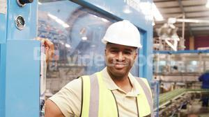Smiling worker operating a machine