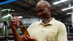 Smiling worker examining a bottle