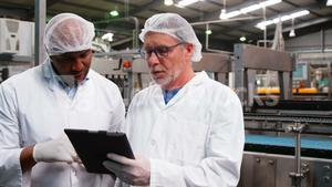 Workers discussing over digital tablet