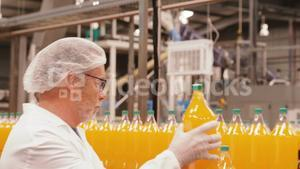 Worker examining a bottle in factory