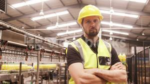 Worker standing with arms crossed in factory