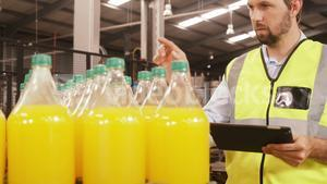 Worker maintaining record on digital tablet while counting bottles