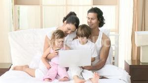 Family in bed using a laptop