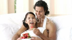 Panorama of couple sitting in bed eating strawberries