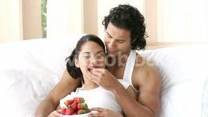 Happy couple sitting in bed eating strawberries