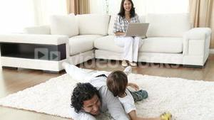 Dad and little boy playing video games and mom using a laptop