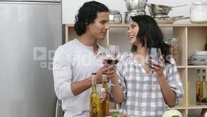 Happy couple eating a salad and drinking wine in the kitchen