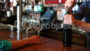Barman opening wine bottle with corkscrew at bar counter