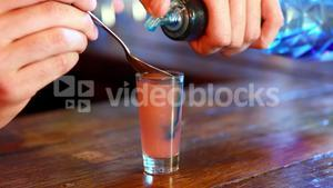 Barman mixing color in tequila at bar counter