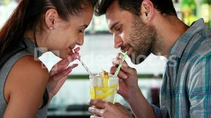 Happy couple sharing milkshake