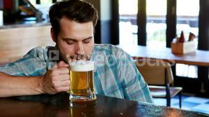 Sad man having beer at bar counter