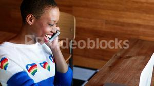 Woman talking on mobile phone while using laptop