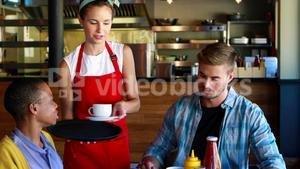 Waitress serving coffee to customers