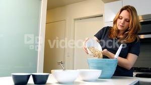 Woman adding ingredients to bowl for baking