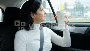 Woman sitting in car holding disposable cup
