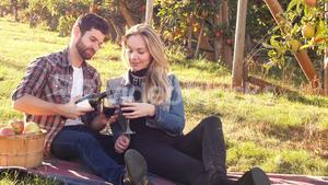 Couple having wine in orchard