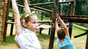 Siblings hanging on a playing equipment in park