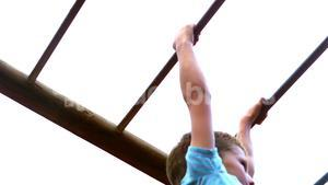 Boy playing on monkey bars in playground