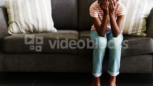 Upset girl sitting on sofa in corridor