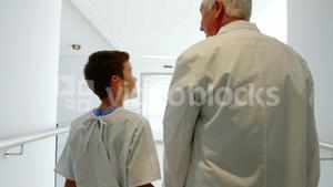 Doctor walking with patient in hospital corridor