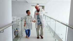 Doctor interacting with patient while walking in corridor