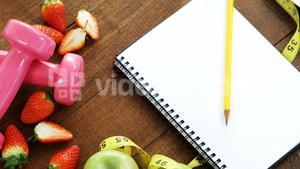Strawberry, measuring tape, dumbbells and spiral notebook on table