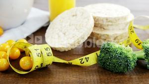 Broccoli, granola bar, yellow cherries and measurement tape on wooden table