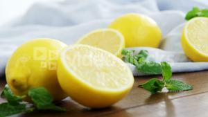 Full and half lemons with mint leaf on table