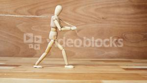 Wooden figurine pulling a rope on wooden floor