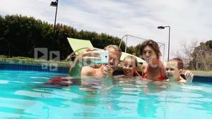 Family talking selfie from mobile phone at pool side