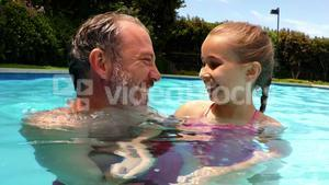 Portrait of father and daughter in swimming pool